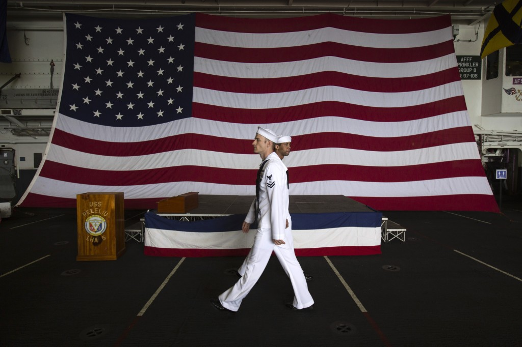 U.S. Navy personnels walk in front of a U.S flag in the amphibious assault ship USS Peleliu (LHA 5) as it docks at Tsim Sha Tsui for routine port visit in Hong Kong April 15, 2013. REUTERS/Tyrone Siu
