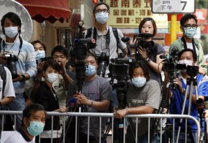 Journalists wearing masks wait behind a fence outside a hotel in which 200 guests and 100 staff were ordered to stay in in Hong Kong