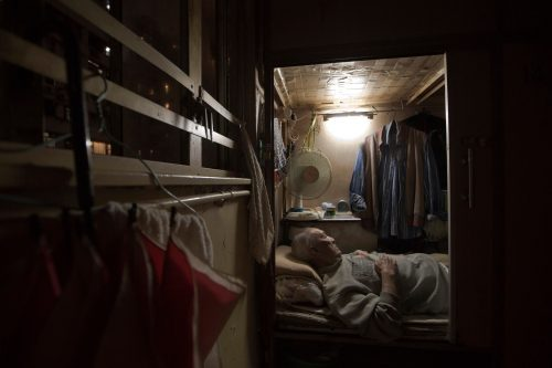 "March 28, 2017 photo, Tse Chu, a retired waiter, sleeps in his ""coffin home"" in Hong Kong. In wealthy Hong Kong, there's a dark side to a housing boom, with hundreds of thousands of people forced to live in partitioned shoebox apartments, ""coffin homes"" and other ""inadequate housing."