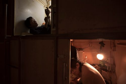 """March 28, 2017 photo, Mr.Yeung, left and Mr.Lui take rest in their """"coffin homes"""" in Hong Kong. In wealthy Hong Kong, there's a dark side to a housing boom, with hundreds of thousands of people forced to live in partitioned shoebox apartments, """"coffin homes"""" and other """"inadequate housing."""