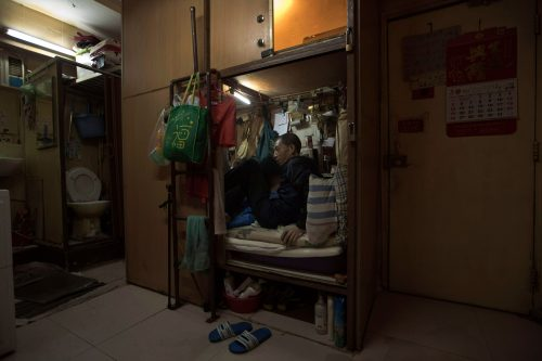"March 28, 2017 photo, Wong Tat-ming, 63, sits in his ""coffin home"" which is next to a set of grimy toilets in Hong Kong as he pays HK$2,400 ($310) a month for a compartment measuring three feet by six feet. It's crammed with all his meager possessions, including a sleeping bag, small color TV and electric fan."