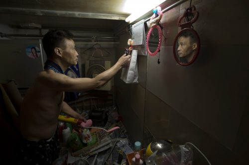 "May 4, 2017 photo, Mr. Sin, 55, tidies up the bed in his ""coffin home"" in Hong Kong. In wealthy Hong Kong, there's a dark side to a housing boom, with hundreds of thousands of people forced to live in partitioned shoebox apartments, ""coffin homes"" and other ""inadequate housing."