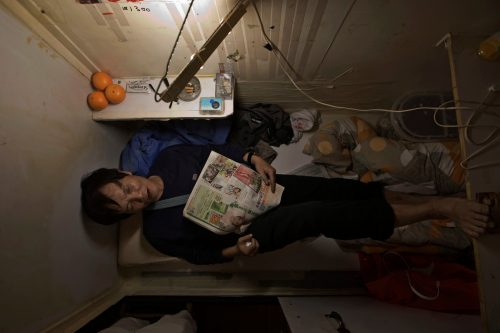"March 28, 2017 photo, Mr.Yeung takes rest in his ""coffin home"" in Hong Kong. In wealthy Hong Kong, there's a dark side to a housing boom, with hundreds of thousands of people forced to live in partitioned shoebox apartments, ""coffin homes"" and other ""inadequate housing."