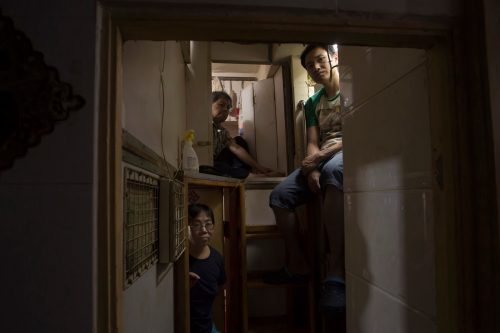 "May 4, 2017 photo, Hong Kong residents Mr. Lam, top left, Mr. Wan, top right, and Kitty Au, pose at their ""coffin homes"" in Hong Kong. In wealthy Hong Kong, there's a dark side to a housing boom, with hundreds of thousands of people forced to live in partitioned shoebox apartments, ""coffin homes"" and other ""inadequate housing."