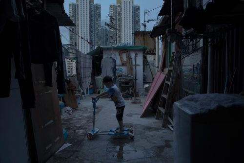April 20, 2017 photo, a five year-old boy plays outside his tiny home which is made of concrete and corrugated metal on the terrace of a apartment block as he lives with his parents in an illegal rooftop hut where is located next to a public housing estate at the background in Hong Kong.