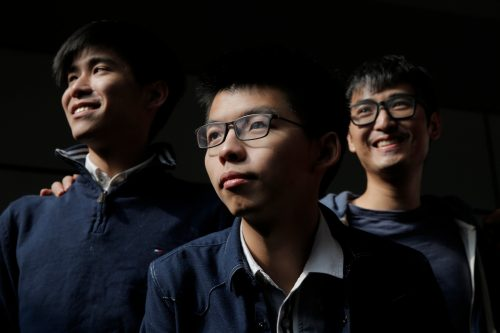 From left, Hong Kong's young democracy leaders Lester Shum, Joshua Wong and Alex Chow pose for photographers in front of the High Court in Hong Kong, Thursday, Dec. 7, 2017. Hong Kong's young democracy leader Joshua Wong faces a possible new prison sentence in a case stemming from 2014 protests in the semiautonomous Chinese city. He's among a group of activists awaiting sentencing Thursday afternoon following their convictions months earlier.